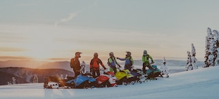 5 guys in snowmobiles on the top of a mountain